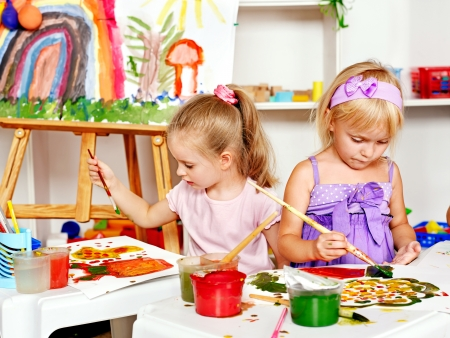 kids drawing: Child painting at easel in school. Education.