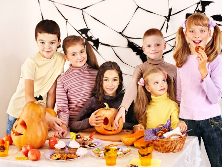 Family on Halloween party with children making carved pumpkin. photo