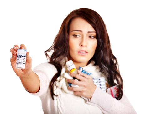 cold remedy: Young woman having pills and tablets. Isolated.