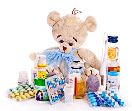 packs of pills: Child medicine and teddy bear. Isolated. Stock Photo