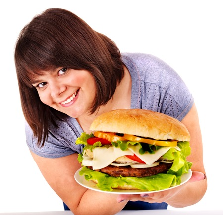 obese woman: Overweight woman eating hamburger. Isolated.