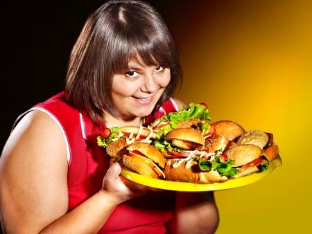 Overweight woman holding hamburger. photo