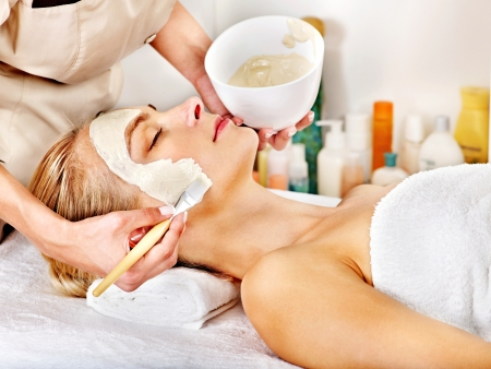 Woman with clay facial mask in beauty spa. Reklamní fotografie