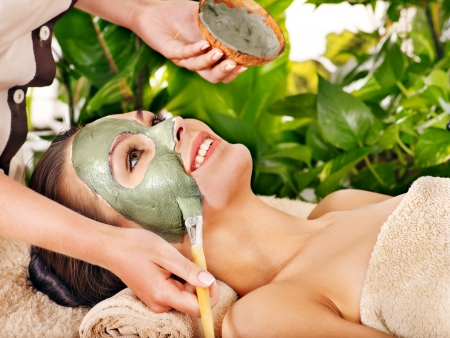 Woman with clay facial mask in beauty spa. Banque d'images
