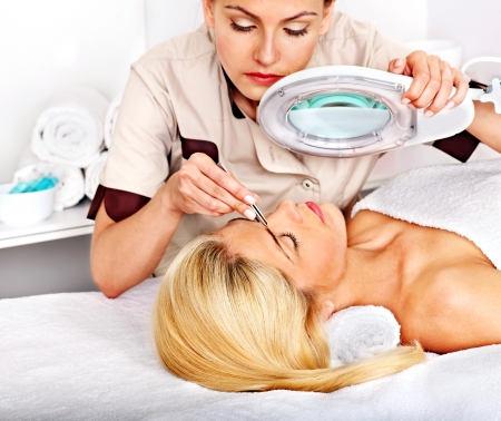 beauty parlour: Woman getting tweezing eyebrow by beautician.