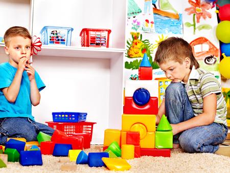 playschool: Little boy  in kindergarten stacking block.