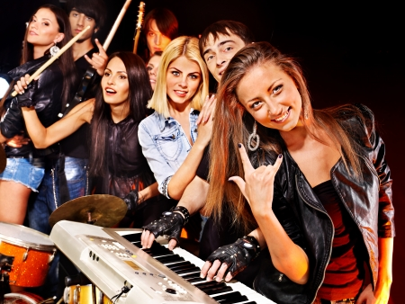 Woman beat guitar: Musical group performance in night club.