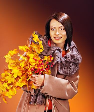 overcoat: Woman wearing overcoat holding  orange leaves. Stock Photo
