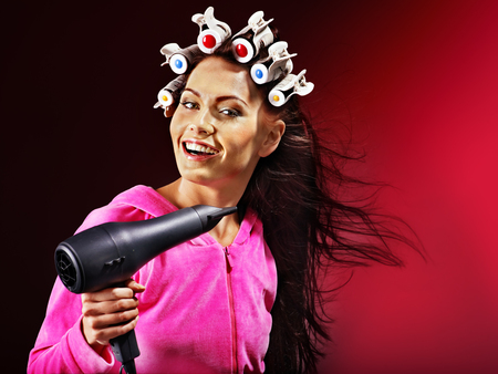 hot rollers: Happy woman wear hair curlers holding  hairdryer.