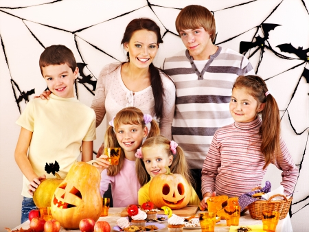 Family on Halloween party with children making carved pumpkin. Stock Photo - 22259320