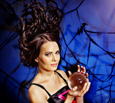 fortune telling: Young woman  with crystal ball. Halloween.