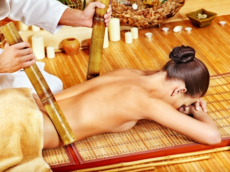 Young woman getting bamboo massage. Male therapist. photo