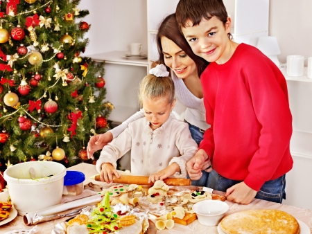 Happy family with children rolling dough in Christmas kitchen