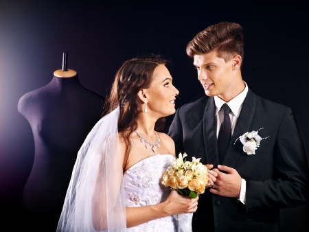 Happy couple try wedding dress in shop. photo