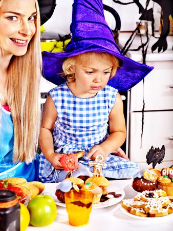 Mother with daughter preparing halloween food.