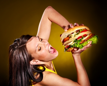 junk: Slim woman holding hamburger  Stock Photo