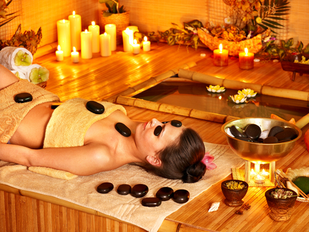 Woman getting stone therapy massage in bamboo spa  photo
