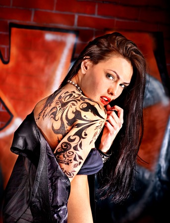 Woman with body art aganist graffiti brick wall  photo