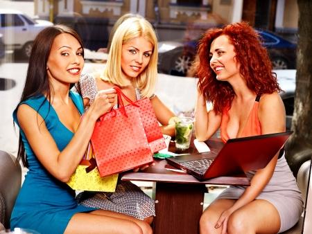 vida social: Chismes mujeres con ordenador port?til en un caf?.