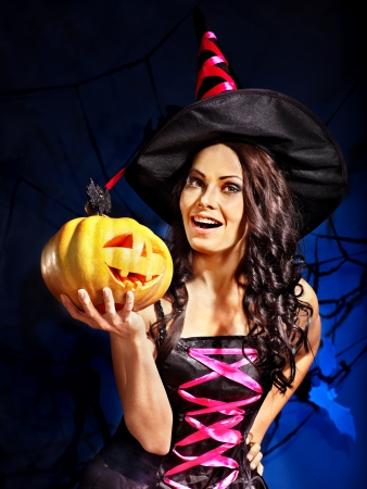 Happy witch holding pumpkin Stock Photo
