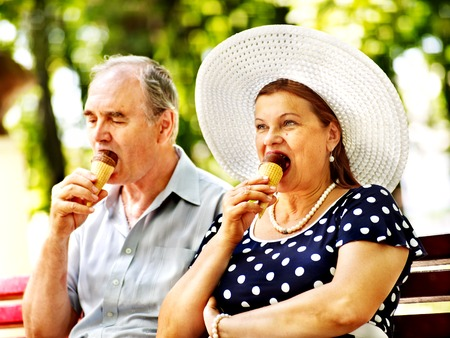 Happy old couple eating ice-cream outdoor. photo