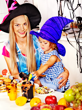 Mother with daughter preparing halloween food. photo
