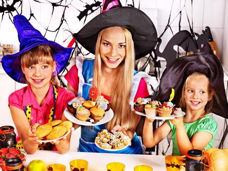Happy family with children preparing halloween food.