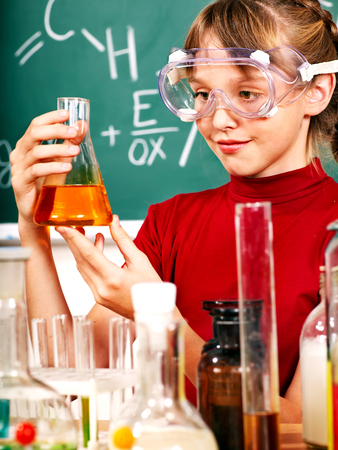 chemistry class: Child holding flask in chemistry class.