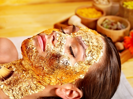beauty care: Woman getting  gold facial mask.