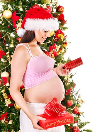 Pregnant  woman holding red Christmas box. photo