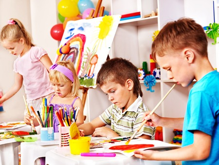 kids club: Children painting at easel in school. Education.