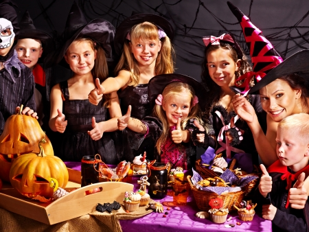 halloween party: Family on Halloween party with children making carved pumpkin. Stock Photo