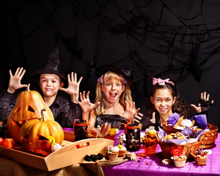 Children on Halloween party  sitting at trick or treat table. Stock Photo