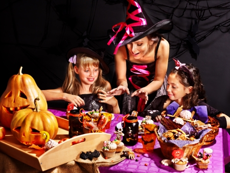 Family on Halloween party with children making carved pumpkin. Stock Photo