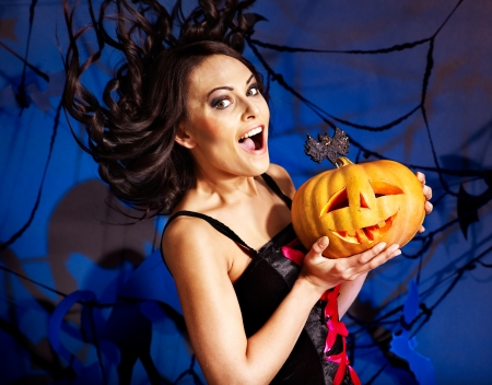 Happy witch holding pumpkin photo