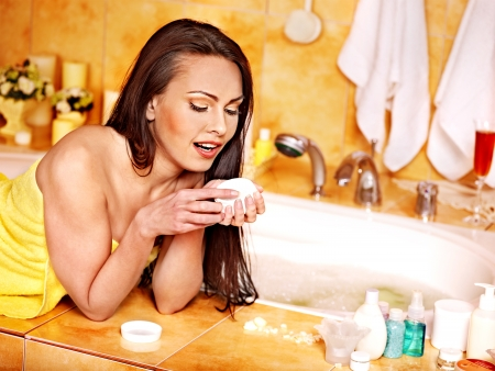 Woman applying moisturizer at bathroom. Stock Photo - 22528550