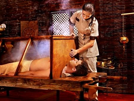 window treatments: Woman having Ayurvedic sauna treatment.