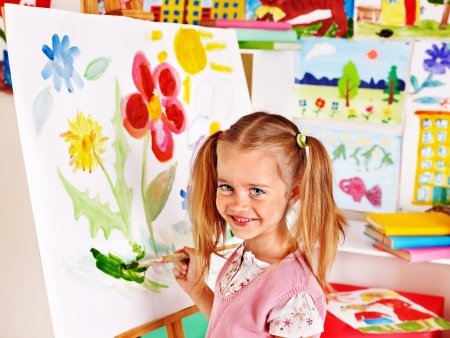 nursery school: Child painting at easel in art class. Stock Photo