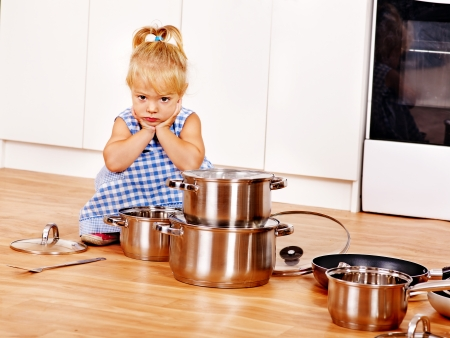Child holdig group pan at kitchen. photo