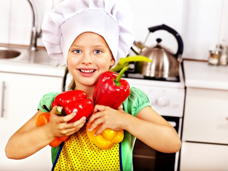 Child holding vegetable at kitchen. photo