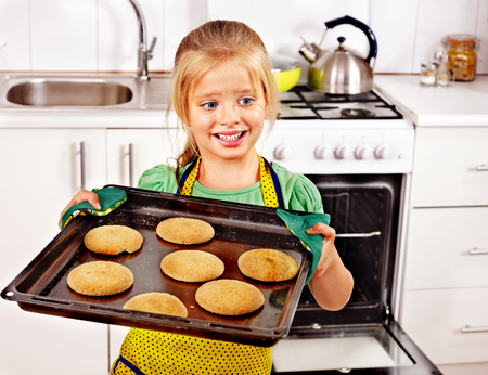 baking oven: Young woman  baking cookies in oven.