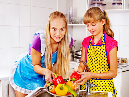 Mother and daughter washing fruit at kitchen. photo