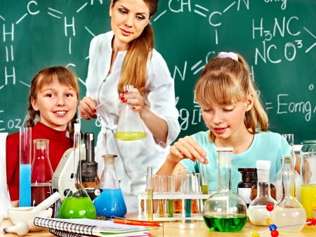 Children and teacher holding flask in chemistry class. photo