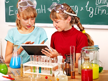 Child holding tablet pc in chemistry class. photo