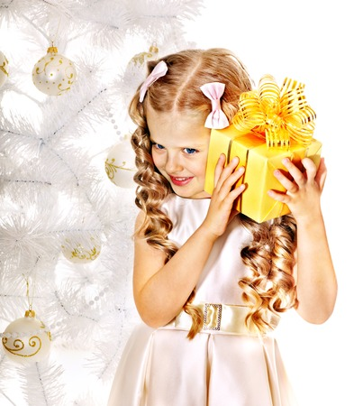 surprise: Child with gift box near white Christmas tree. Isolated.