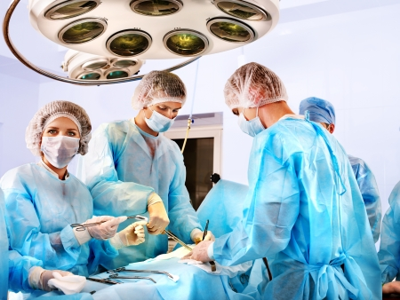 surgeon operating: Team surgeon at work in operating room.