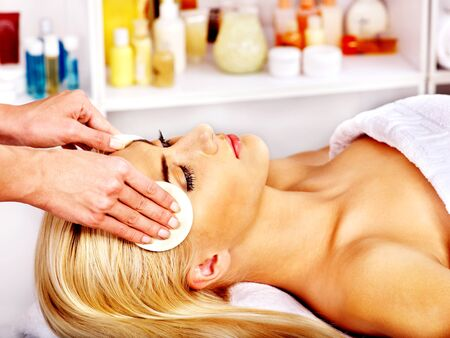 Blond woman getting head massage at spa. photo