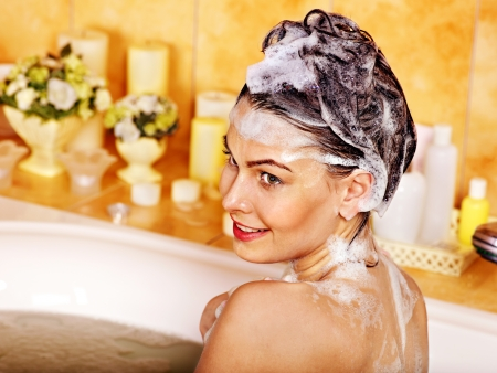 woman washing hair: Woman washing hair in bubble bath. Stock Photo