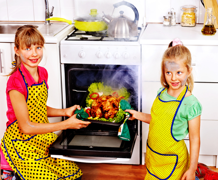 Children with  burned chicken cooking at kitchen. photo