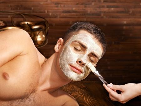 masajes faciales: Hombre con m?scara facial de barro en el spa de belleza.